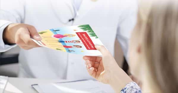 Arzt übergibt Kind Patientenbroschüre