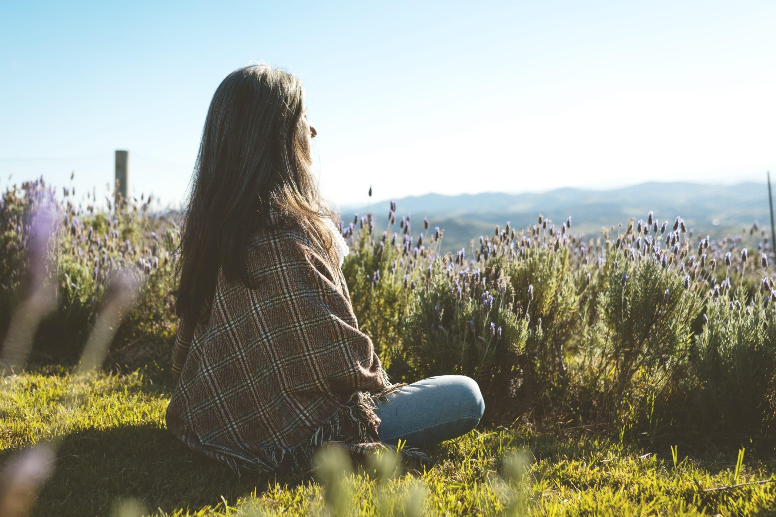 Junge Frau sitzt in der Natur und blickt in die Ferne